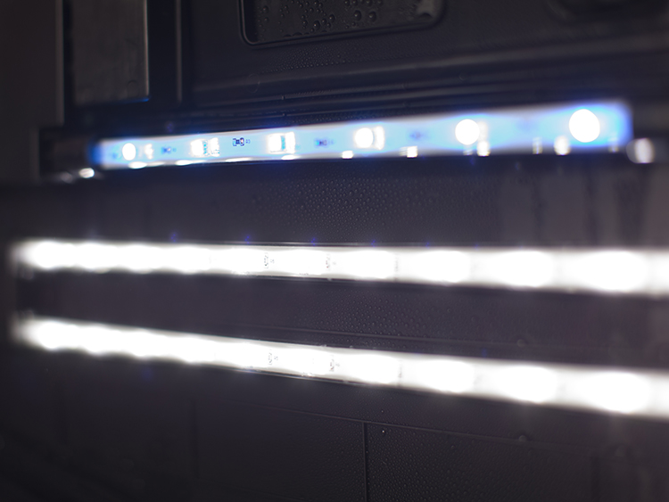 Close up of LED lighting bars in a black aquarium hood. 2 white, 1 blue light